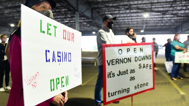 Cyndi Minckler, an operations supervisor at Vernon Downs Casino, holds a sign with others during an August rally that was hosted to encourage Gov. Cuomo to reopen privately owned casinos in the state. Cuomo said Sept. 3 that casinos could start to reopen Wednesday with a variety of safety measures and limited capacity.