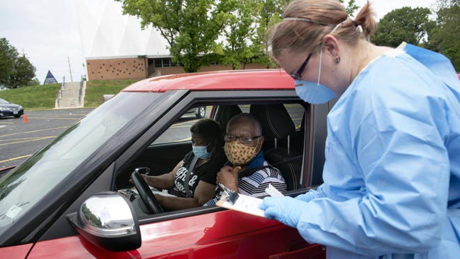 Care STL nurse Amy Heidotten, right, takes information from Eleanor James, left and her husband Maxwell James at a free coronavirus testing site June 5 at Christ the King United Church of Christ in Florissant.