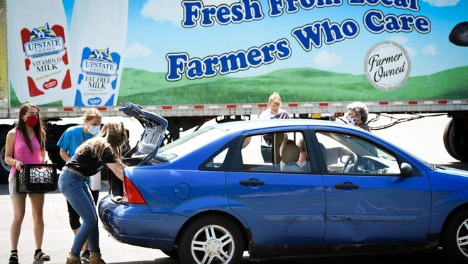 In this file photo from June 2020, Connie Frasier, Stephanie Treadwell and Victoria Treadwell load gallons of milk into a vehicle at Herkimer Jr./Sr. High School. The office of Legislator Robert Schrader and the Herkimer County Legislature partnered with American Dairy Association North East to organize a free dairy drive-thru.