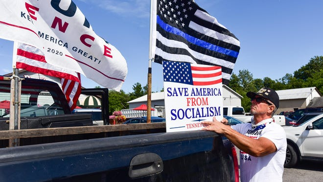 Tim Muller decorates the back of his pickup truck during a rally hosted in support of President Donald Trump in New York state. Supporters of the president are planning a caravan event Sunday, Sept. 27, 2020, starting in Portsmouth and traveling around the Seacoast.