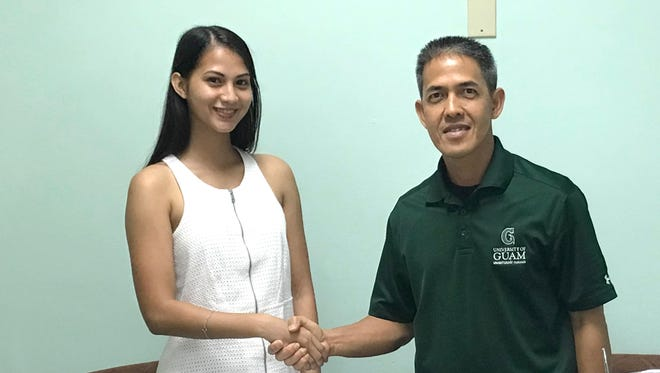 Megan Gay shakes hands with University of Guam women's soccer head coach Rod Hidalgo after committing to play for the Tritons.