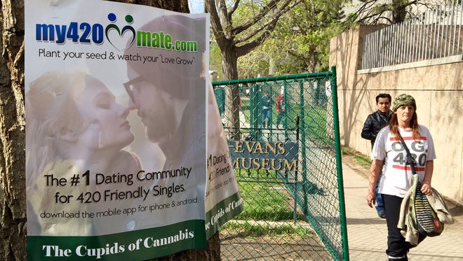 People leaving a marijuana festival April 19, 2015, in downtown Denver walk past an advertisement for a marijuana-themed dating site that calls itself The Cupids of Cannabis.