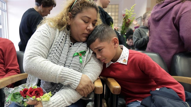 "Olga Grays comforts her son, Angel Herrera, 9, as the photo of her husband and Angel's stepfather, Roger Grays, is added to the Wall of Heroes on Wednesday at University Medical Center of El Paso. Grays, an assistant coach at Centennial High School in Las Cruces, died in a car accident last November. He was honored for being an organ donor at the annual event. ""Roger was so full of life,"" Grays said. ""And even after he passed away he's giving life to other people."" The event was bittersweet for the families of the donors who were honored. ""It brings a little bit of happiness to my heart, as hard as it is, to know how many lives he touched,"" Grays added. The other three donors honored were Arianna Archuleta, Timothy Simpson and Bruce Mathews."