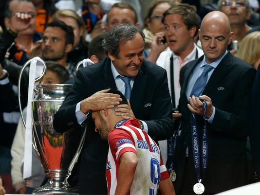 Atletico's David Villa, is patted on the head by UEFA president Michel Platini, after receiving his runner up medal,  at the end of the Champions League final soccer match between Atletico Madrid and Real Madrid, at the Luz stadium, in Lisbon, Portugal, Saturday, May 24, 2014. (AP Photo/Daniel Ochoa de Olza)