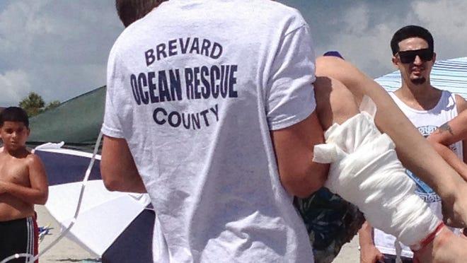 Brevard Ocean Rescue responders transport a juvenile shark bite victim at Lori Wilson Park in Cocoa Beach.
