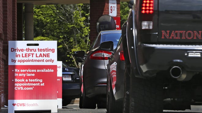 FILE - Cars idle in line as patients wait to self-take a COVID-19 virus test at a drive thru for the CVS Pharmacy in Danvers, Mass., Friday, May 15, 2020. CVS has expanded their testing sites.