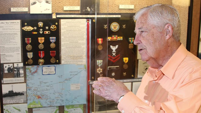 Roy Johns is a founder at Chennault Museum. He stands in front of a display of his personal items from his service in World War II.