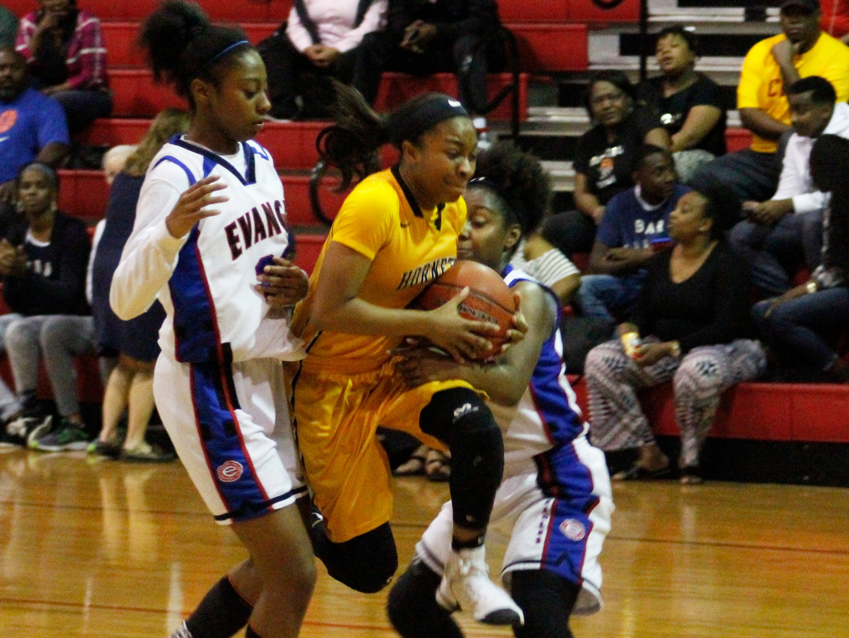 A Scotlandville player forces her way between Evangel's Tiara Young (left) and Madison Laboy. The Lady Hornets won the game.