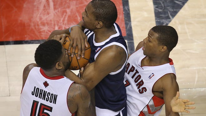 Oklahoma City Thunder forward Kevin Durant (35) battles for control of the ball against Toronto Raptors forward Amir Johnson (15) and point guard Kyle Lowry (7) at Air Canada Centre. The Thunder beat the Raptors 119-118 in double overtime Friday. Mandatory Credit: Tom Szczerbowski-USA TODAY Sports
