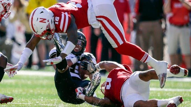 Purdue running back Markell Jones, back center left, makes a catch against Nebraska safety Antonio Reed (16), and linebacker Dedrick Young II (5) during the first half of an NCAA college football game in Lincoln, Neb., Saturday, Oct. 22, 2016.