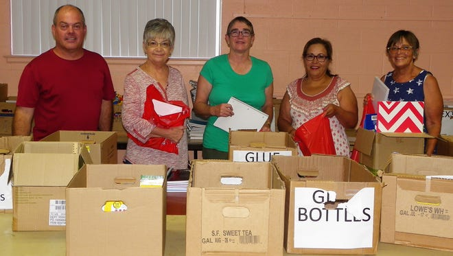 "From left Youth and Young Adult Minister Alan McMillen, June Hatcher, Cheryl Dockeray, Josie Amaya and Cathy Leedyfill red bags with school supplies for  Love, INC's ""Tools for School"" giveaway."