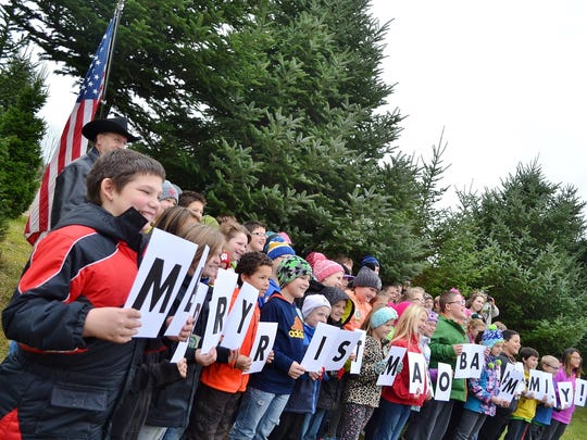 """Students from Tank Elementary School in Green Bay hold up letters saying """"Merry Christmas Obama Family"""" during a tree-cutting ceremony for the official White House Christmas Tree in Oconto."""