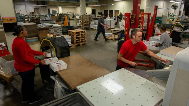 Employees at Mainline Printing, 3500 S.W. Topeka Blvd., work in the binding area of the print shop Thursday afternoon. The company announced in a news release Thursday that it has purchased the print assets of Go Modern, another local company offering printing and marketing services.