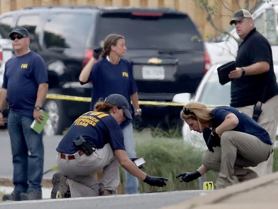 Investigators look for evidence in a parking next to