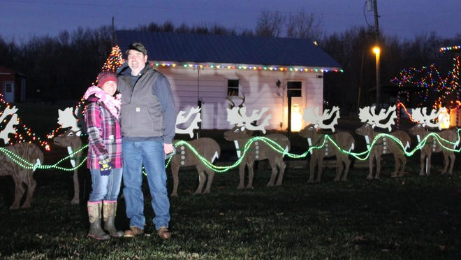 Crystal and Mike Perry on Maystead Road, Burr Oak, spend time in the cold to light he neighborhood with Christmas cheer.