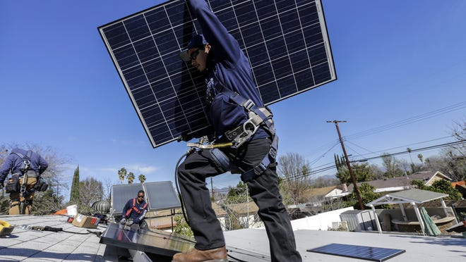 Alejandro DeLeon carries a solar panel as workers from home solar company Sunrun install a system on a home in Los Angeles.