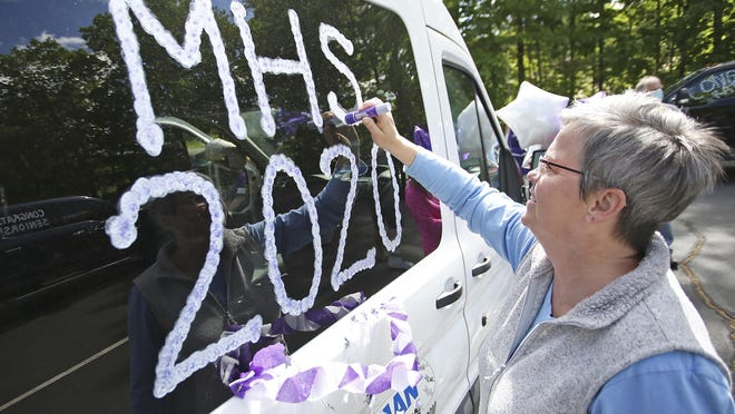 Parent Andrea Bingham decorates a van Monday morning at Marshwood High School. Parent volunteers and members of the Marshwood Project Graduation Committee gather to decorate vehicles for the first of many senior week surprises. Teachers will be delivering gift baskets, including a T-shirt, sweatshirt, car decorating items and movie tickets to all seniors.