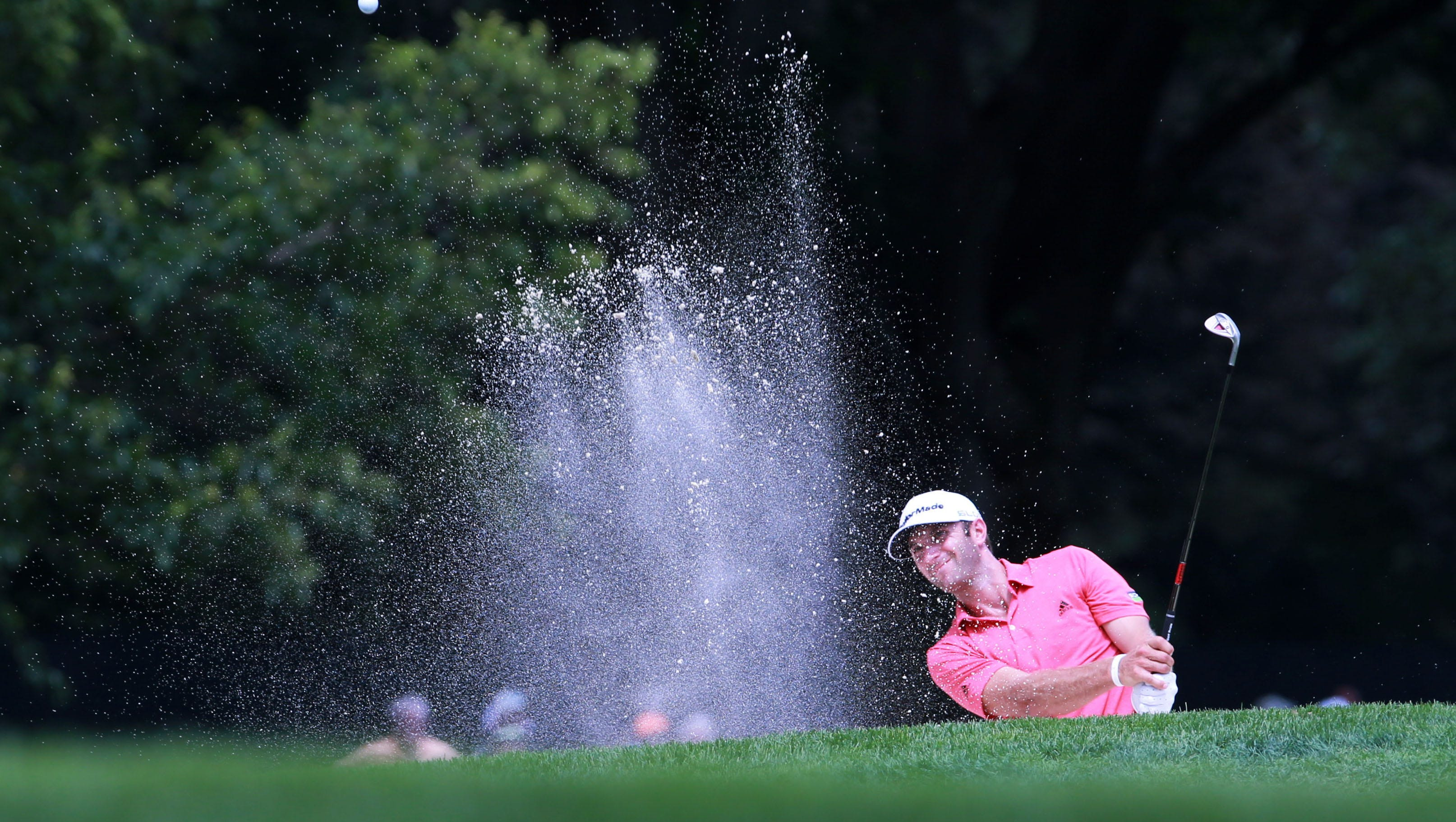 Dustin Johnson plays out of a bunker on the 8th hole.