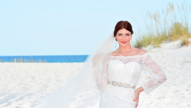Model: Kimberly Battista. Sheer off-the-shoulder neckline, long sleeves, scalloped accents on the neckline and hemline, elegant non-beaded stretch lace over silk satin, and â??Vâ? back with satin buttons, Designs by Renee, style number LR0003, $1,300; cathedral veil with Swarovski crystals, $275; belt with Swarovski crystals, $275; and elongated teardrop earrings with Swarovski crystals, $95, all at Reneeâ??s Bridal and Special Occasions.