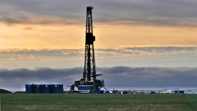 An oil-drilling rig sprouts from the landscape northeast of Williston, N.D., just after dawn May 19 as the workday already has begun.