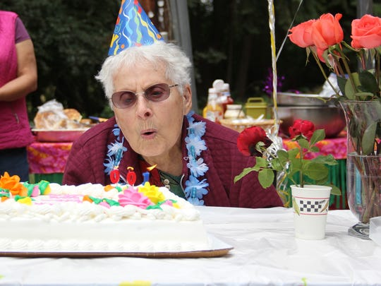 Verna Scharbach blows out candles celebrating her 100th