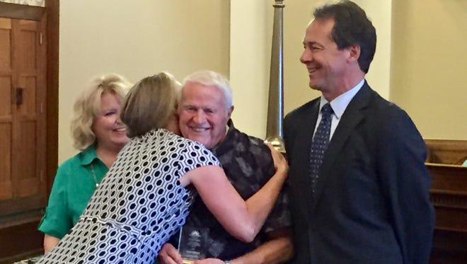 First lady Lisa Bullock hugs Harold Spilde on Friday as Gov. Steve Bullock looks on.