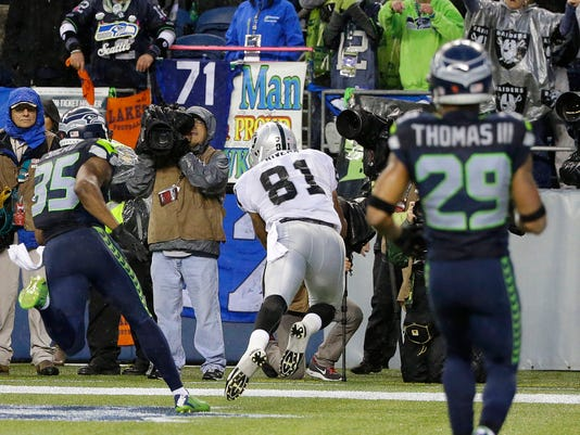 Oakland Raiders tight end Mychal Rivera (81) makes a catch for a touchdown in the second half of an NFL football game against the Seattle Seahawks, Sunday, Nov. 2, 2014, in Seattle. (AP Photo/Elaine Thompson)