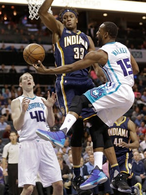 Charlotte Hornets' Kemba Walker (15) passes the ball around Indiana Pacers' Myles Turner (33) to Cody Zeller (40) in the first half of an NBA basketball game in Charlotte, N.C., Monday, March 6, 2017. (AP Photo/Chuck Burton)