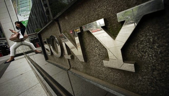 A woman sits near the logo of Sony Corp. in Tokyo on April 30, 2015.