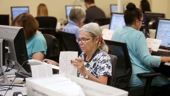 Jeanette Smith verifies signatures on early ballots at the Pima County Recorder's office, 6550 South Country Club Road on May 18, 2016.