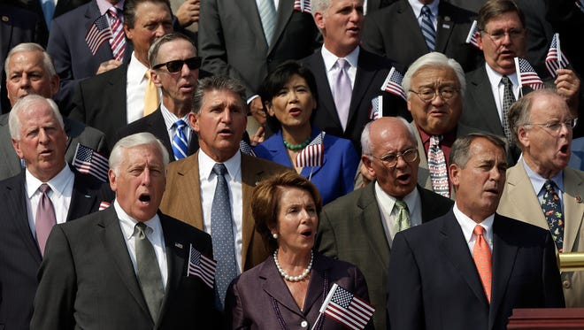 "Members of Congress wave American flags as they sing ""God Bless America"" on the U.S. Capitol steps in 2013."