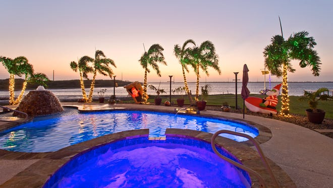 A stunning sunset view of the pool and grounds overlooking Oso Bay