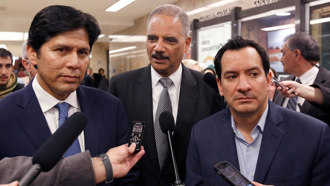 In this Feb. 7 file photo, former U.S. Attorney General Eric Holder, center, flanked by California Senate President Pro Tem Kevin de Leon, D-Los Angeles, left, and Assembly Speaker Anthony Rendon, D-Paramount, talks to reporters before meeting with Gov. Jerry Brown in Sacramento.