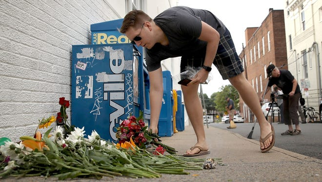 A man places flowers at a makeshift memorial Sunday for the victims of yesterday's attack where a car plowed into a crowd of demonstrators opposing a nearby white nationalist rally on Saturday in Charlottesville, Va.