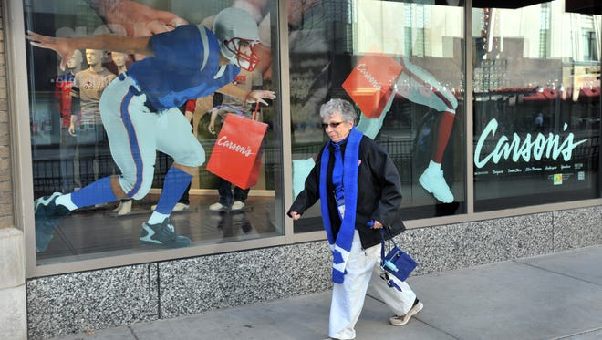 A sports graphic in a display window of Carson Pirie Scott seems to be leaping out at a passing woman on Washington Street, as downtown was crowded with people going to Super Bowl Village and the NFL Experience Monday January 30, 2012.  Joe Vitti / The Star