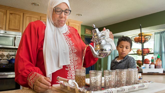 Omar Jacobs, 8, looks on as his mother Rachida pours traditional Moroccan mint tea at their home in Molino on Sunday, May 6, 2018.