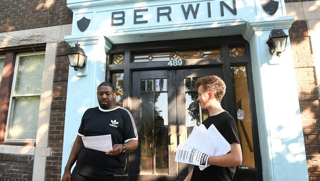 Handing out and posting information about an upcoming Detroit City Council meeting, volunteer Mark Hall, right, talks with resident Brooks Harris, 37, who live in the Berwin apartment building on Henry Street on Sunday.