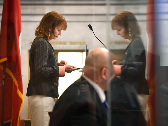 House Speaker Beth Harwell is reflected in glass at
