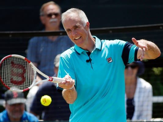 """FILE - In this July 19, 2015, file photo, International Tennis Hall of Fame CEO Todd Martin plays in an exhibition doubles match at the Hall of Fame in Newport, R.I. Martin, who calls barely missing out on the chance to represent the U.S. in singles at Atlanta in 1996 """"one of my great disappointments,"""" thinks Olympic tennis """"needs to do something different to make it look like something different, because it is something different."""" (AP Photo/Michael Dwyer, File)"""