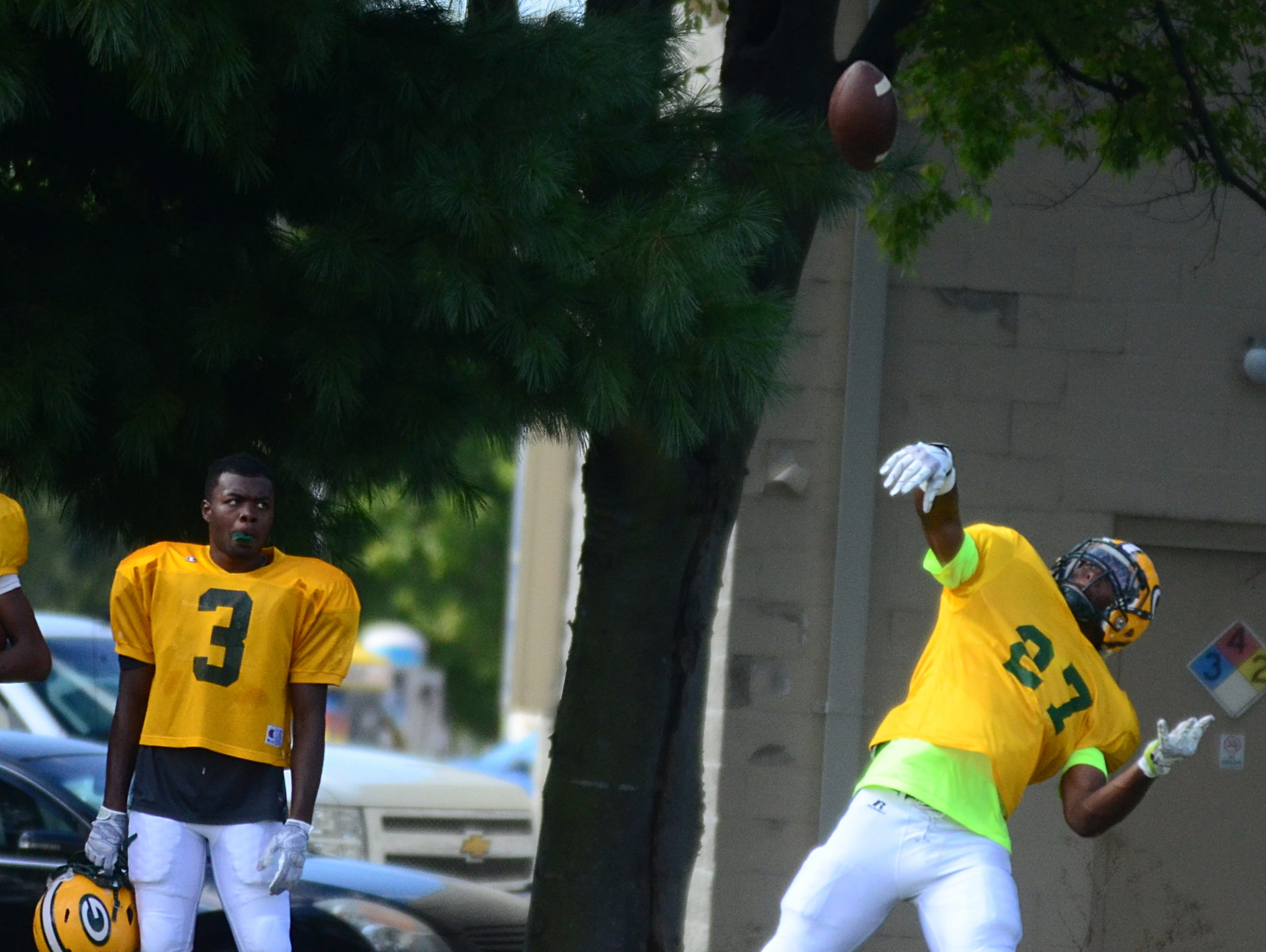 Gallatin senior running back Jordan Mason throws a pass during a break in practice as classmate Marcus DeVault looks on during Tuesday's practice session.
