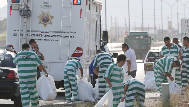 El Paso County Jail Annex inmates pick up debris left along Montana Avenue after Monday evening's Fourth of July celebrations in Montana Vista.