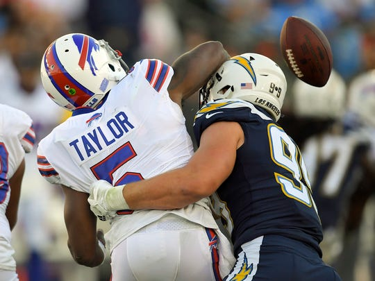 Los Angeles Chargers defensive end Joey Bosa, right, forces a turn over by Buffalo Bills quarterback Tyrod Taylor during the second half of an NFL football game, Sunday, Nov. 19, 2017, in Carson, Calif. (AP Photo/Mark J. Terrill)
