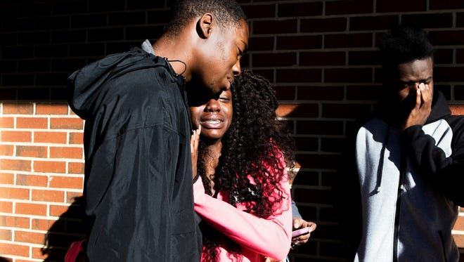 Junior Jaylen Hamilton, senior Kyana Manning and junior LeVonte Abbott, all of Farmerville, La., cry as they stand near the site where another student and his friend visiting from Farmerville were killed Oct. 25, 2017, on the campus of Grambling State University in Grambling, La.