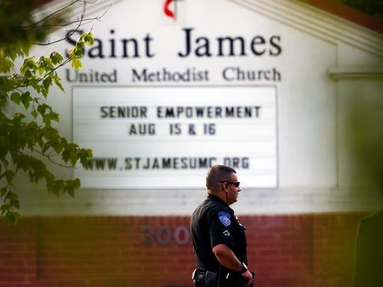A police officer stands guard at the entrance to St. James United Methodist Church before funeral services for Bobbi Kristina Brown Saturday, Aug. 1, 2015, in Alpharetta, Ga.