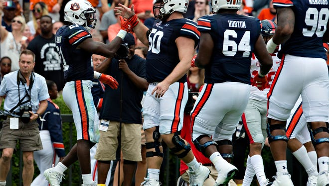 Auburn running back Kerryon Johnson (21) celebrates with Auburn offensive lineman Casey Dunn (50) after scoring during the NCAA football game between Auburn and Ole Miss on Saturday, Oct. 7, 2017, in Auburn, Ala.