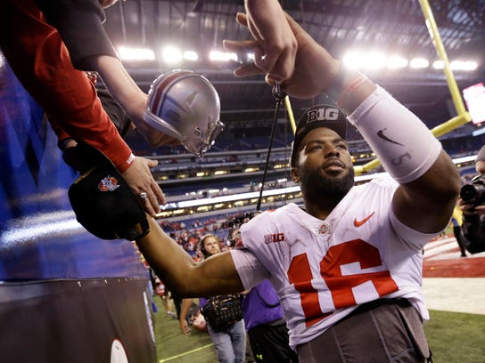 Ohio State's J.T. Barrett celebrates with fans following the team's Big Ten championship NCAA college football game against Wisconsin, early Sunday, Dec. 3, 2017, in Indianapolis. Ohio State won 27-21. (AP Photo/AJ Mast)