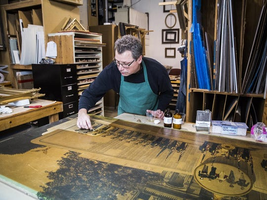 Co-owner Carl Schafer works on cleaning a photo of World War I veterans at Gordy Fine Art and Framing Co.