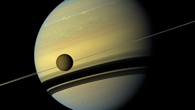 An image provided by NASA shows Saturn's largest moon Titan passing in front of the giant planet in an image made by  NASA's Cassini spacecraft.  The natural color view of Saturn and one of it's moons was made by Cassini's wide-angle  camera on May 6, 2012 and released by NASA on Wednesday Aug. 29, 2012.