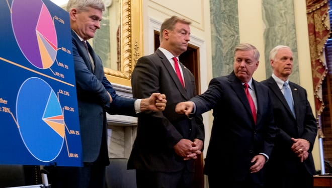 Sens. Bill Cassidy, left, and Lindsey Graham, second from right, accompanied by Sens. Dean Heller and Ron Johnson, fist bump each other during a news conference on Capitol Hill on Sept. 13, 2017, to unveil their health care legislation.