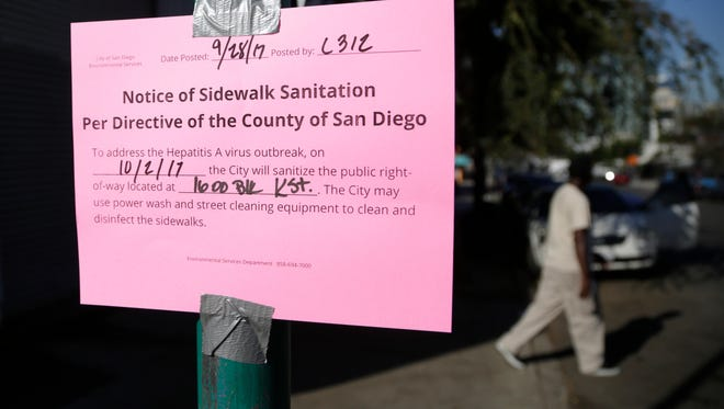 In this file photo, a man passes behind a sign warning of an upcoming street cleaning in San Diego due to a hepatitis outbreak in the city.